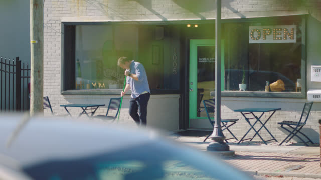vidéos et rushes de owner of an ice cream parlor sweeps the sidewalk in front of his shop - authenticité