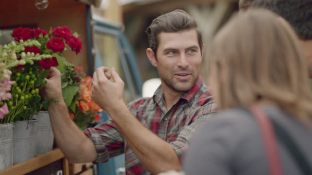 vídeos de stock, filmes e b-roll de owner of mobile flower truck shows flowers to customers at farmers market - bouquet