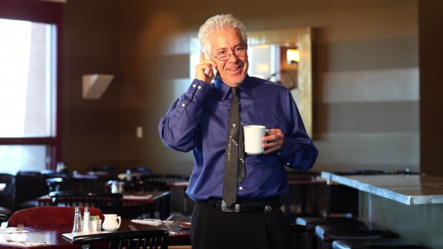 ms owner of restaurant talking on the phone and having coffee / santa fe, new mexico, united states - gastwirt stock-videos und b-roll-filmmaterial