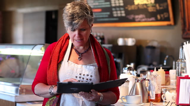 ms owner of restaurant working on her tablet / santa fe, new mexico, united states - gastwirt stock-videos und b-roll-filmmaterial