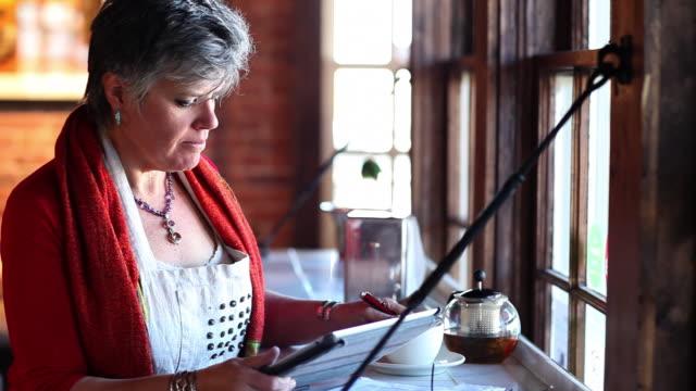 vídeos de stock e filmes b-roll de ms owner of restaurant working on her tablet / santa fe, new mexico, united states - chaleira de chá