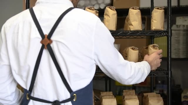 owner stocks coffee bags on the shelf at coffee shop - removing stock videos & royalty-free footage
