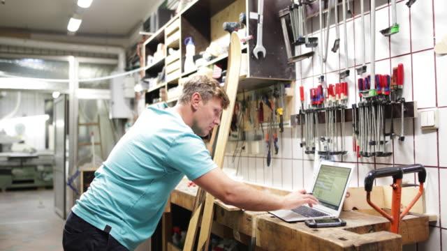Owner using laptop in snowboard workshop