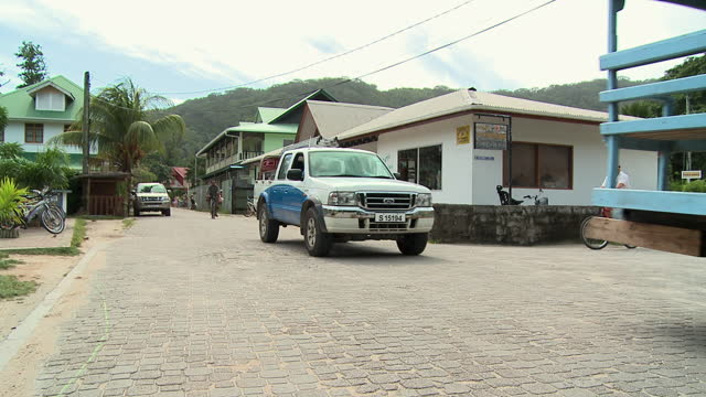 ms ox cart and car on cobblestone street at la digue island, seychelles - ox cart stock videos & royalty-free footage