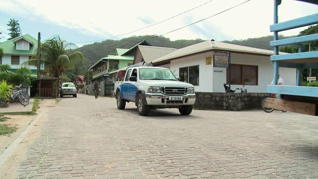 vídeos y material grabado en eventos de stock de ms ox cart and car on cobblestone street at la digue island, seychelles - seychelles