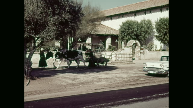 ws ox cart led by monks past spanish style building, chevrolet car drives up and parks / united states - ox cart stock videos & royalty-free footage