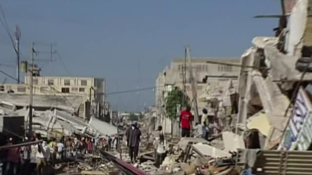 vídeos de stock e filmes b-roll de penny mordaunt to meet national crime agency chief t14011026 / haiti portauprince ext wide shot collapsed building behind fence destroyed building... - escombros material