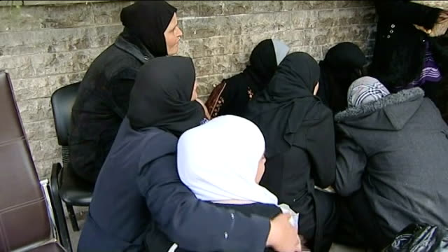 Oxfam launches Syria refugee appeal T21011305 / TX Damascus Yarmouk EXT Women crouching as gunfire heard SOT Woman holding hand to head Women...