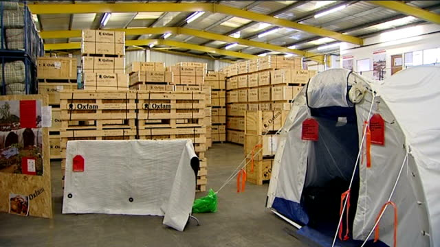 vídeos de stock e filmes b-roll de bicester: int man counting boxes in warehouse and oxfam crates piled high emergency supplies for haiti including tents and pipes and pumps piled high... - hispaniola