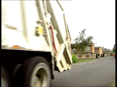 vidéos et rushes de oxford lms dustcart towards past on residential street dustmen throwing rubbish bags into bin lorry ms man throwing rubbish into back of van ms man... - camion poubelles