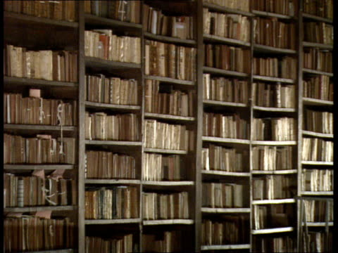 oxford university appeals for cash; itn england: oxford: bodlian library: int ms julian roberts selects ancient book from shelf, seated at table... - oxford university stock videos & royalty-free footage