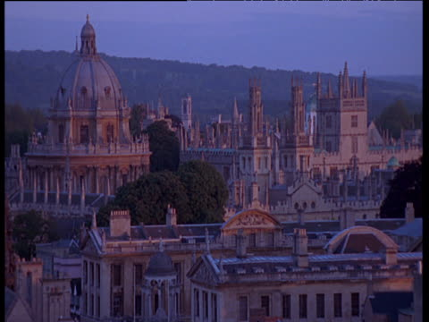 oxford university at sunset causing slightly pink glow, birds fly past in distance - oxford england stock videos and b-roll footage