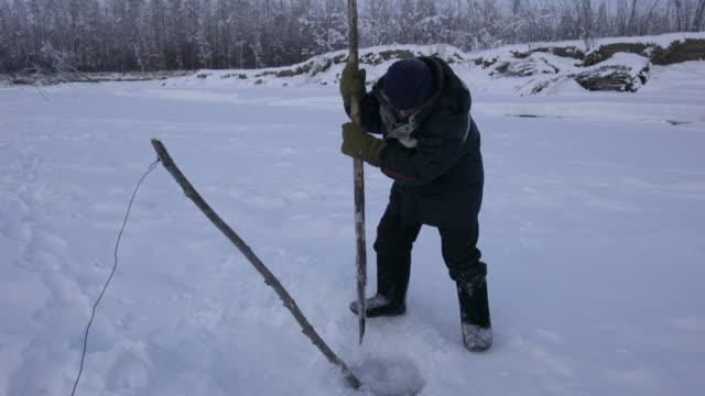vídeos de stock e filmes b-roll de oymyakon, sakha republic , russia; february 18, 2020: ice-fishing on the indigirka river near the village of oymyakon, the pole of cold, is a common... - peixe congelado