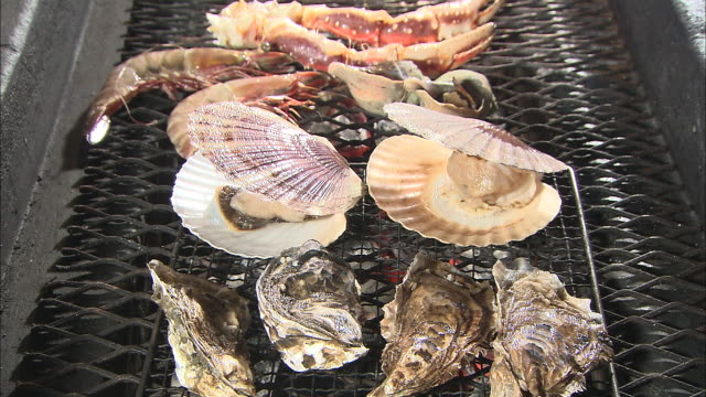 Oysters, king crabs, whelks and scallops grill on a charcoal fire.