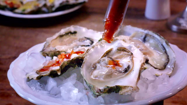 oysters on plate with tabasco sauce and lemon - crustacean stock videos & royalty-free footage