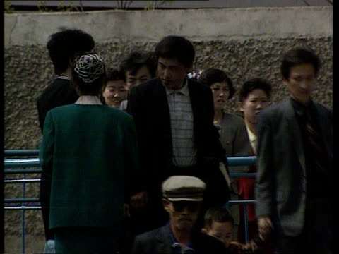 north korea pyongyang tbv group of men seated on ground playing board game pieces on board cms men sitting playing lms people to and fro in front of... - communist flag stock videos and b-roll footage