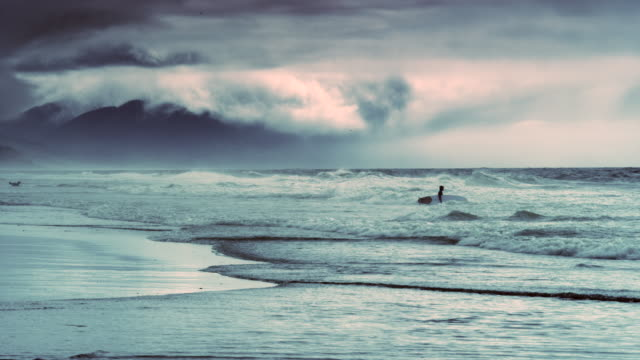 pacific city state park beach oregon with surfer and storm at sunset - oregon us state stock videos and b-roll footage