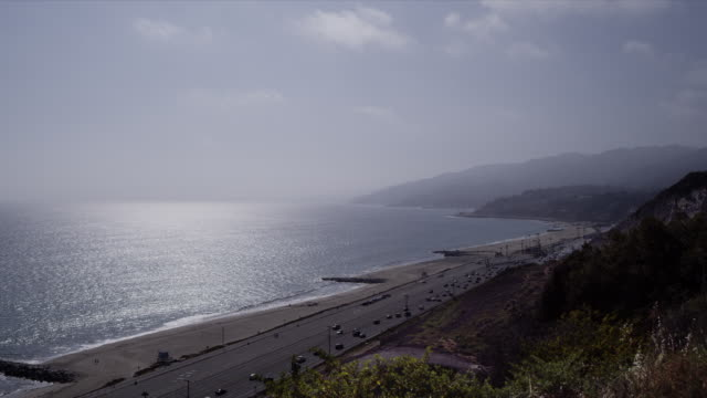pacific coast highway and will rogers beach, glimmering ocean, blue skies, malibu coastline in distance - malibu beach stock videos & royalty-free footage