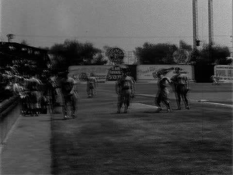 pacific coast league baseball team, the hollywood stars, emerging from dugout, running onto baseball diamond, mostly empty bleachers at gilmore field... - pacific war stock-videos und b-roll-filmmaterial