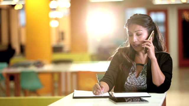 Pacific Islander businesswoman talking on phone, writing