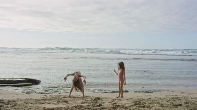 pacific islander children doing acrobatic moves on beach - na pali coast state park stock videos & royalty-free footage