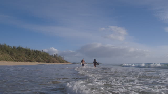 pacific islander couple jogging with surfboards in waves - french overseas territory stock videos & royalty-free footage