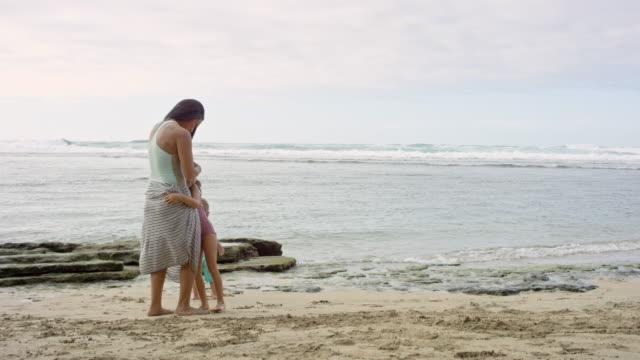 pacific islander daughter giving mother hug on beach - pacific islander stock videos & royalty-free footage