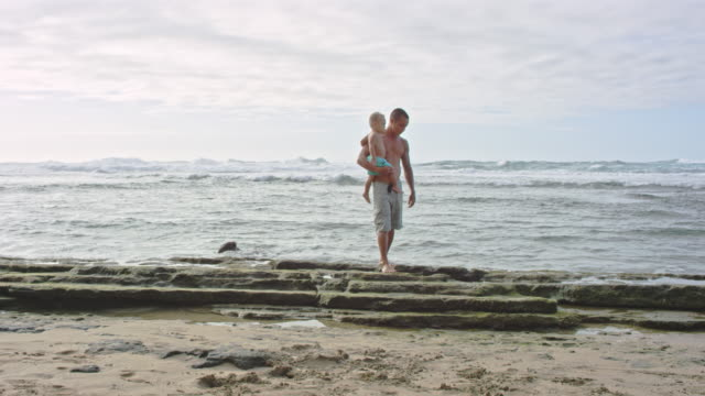 pacific islander father holding son next to ocean - pacific islander stock videos & royalty-free footage