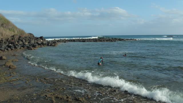 pacific islander man and woman entering ocean to snorkel - pacific islander stock videos & royalty-free footage