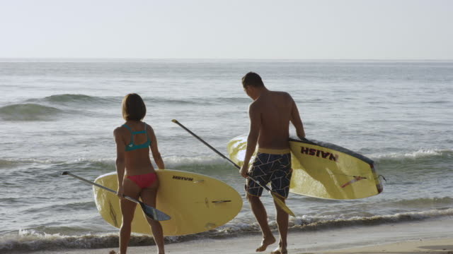 Pacific islander man and woman entering water with SUP boards