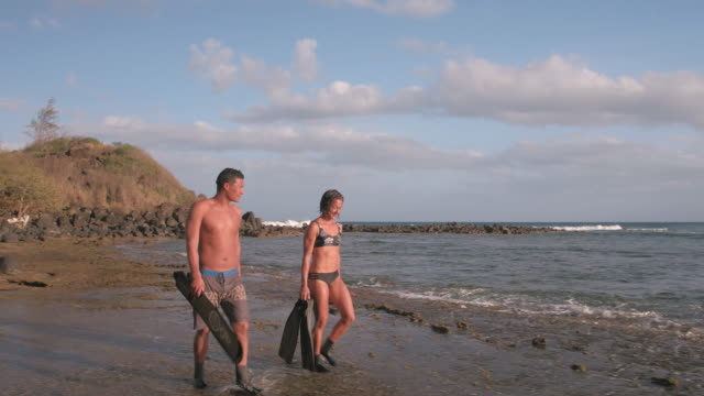 Pacific Islander man and woman walking along beach with snorkel gear