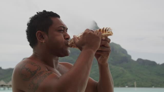 pacific islander man blowing a conch - pacific islander stock videos & royalty-free footage