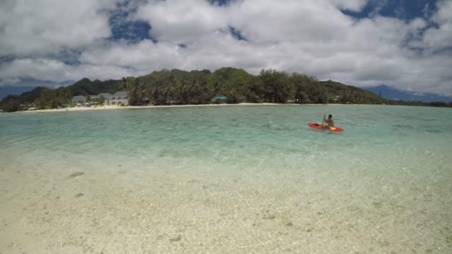 pacific islander man kayaking over muri lagoon rarotonga cook islands - rarotonga stock videos & royalty-free footage