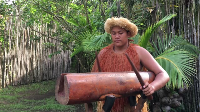 Pacific Islander man plays music on a large wooden log Pate drum instrument in Rarotonga Cook Islands