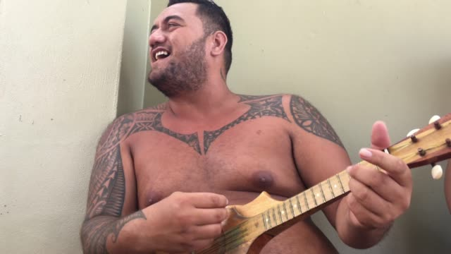 Pacific Islander man sing and plays music on Ukulele Guitar