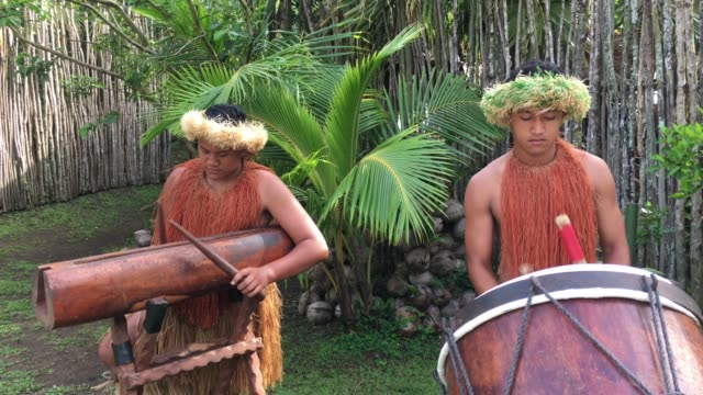 Pacific Islander men plays music on a large wooden drums in Rarotonga Cook Islands