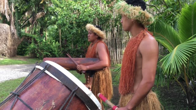 vídeos de stock, filmes e b-roll de pacific islander men plays music on a large wooden drums in rarotonga cook islands - arte, cultura e espetáculo