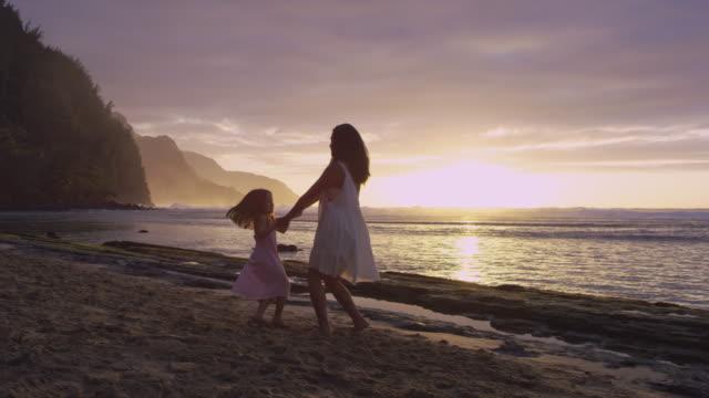 pacific islander mother swinging daughter on beach - pacific islander stock videos & royalty-free footage