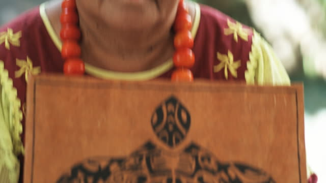 stockvideo's en b-roll-footage met pacific islander woman holding local artwork - tropische boom