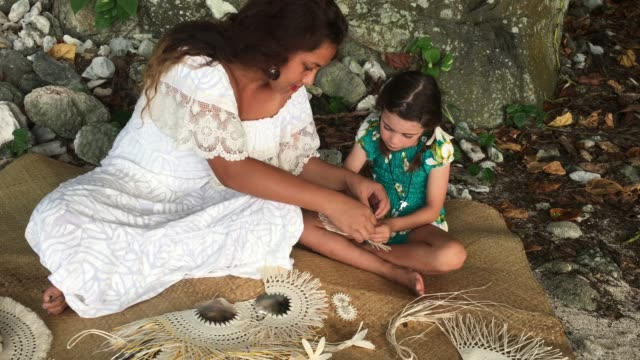 Pacific Islander woman show to a tourist girl how to weave a hand fan in Rarotonga Cook Islands