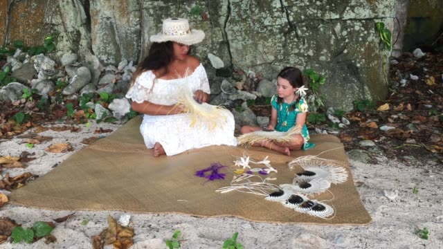 pacific islander woman show to a tourist girl how to weave a hand fan in rarotonga cook islands - rarotonga stock videos & royalty-free footage