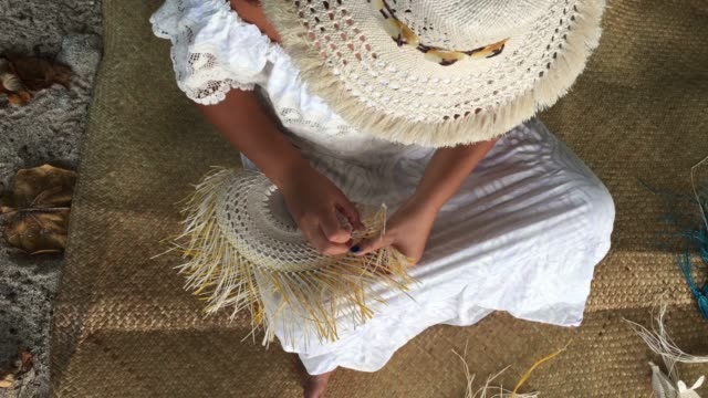 Pacific Islander woman wearing a Rito hat, weaving a hand fan in Rarotonga, Cook Islands