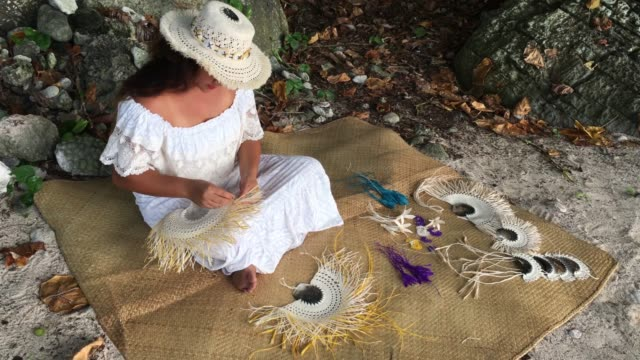 pacific islander woman wearing a rito hat, weaving a hand fan in rarotonga, cook islands - polynesian ethnicity stock videos & royalty-free footage
