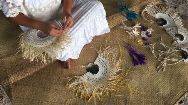 Pacific Islander woman wearing a Rito hat, weaving a hand fan in Rarotonga, Cook Islands