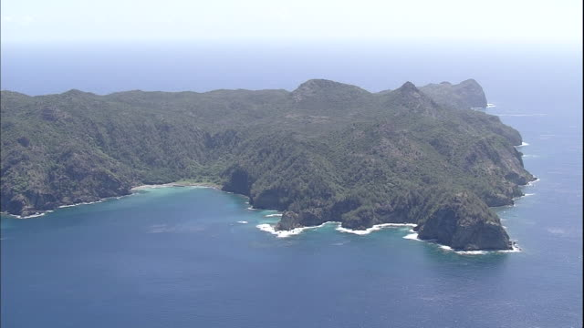 pacific ocean waves crash onto the rocky cliffs of anijima island - subtropical climate stock videos and b-roll footage