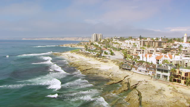 WS AERIAL POV Pacific Ocean with San Diego residential neighbourhood along rocky coastline with high white cliffs in background / San Diego, California, United States