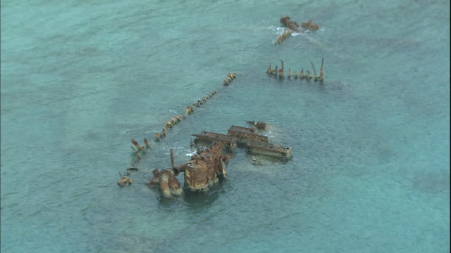 vidéos et rushes de pacific waters wash over the wreckage of the world war ii cargo ship, hinko maru, torpedoed and grounded during the pacific theater on chichijima island, japan. - endommagé