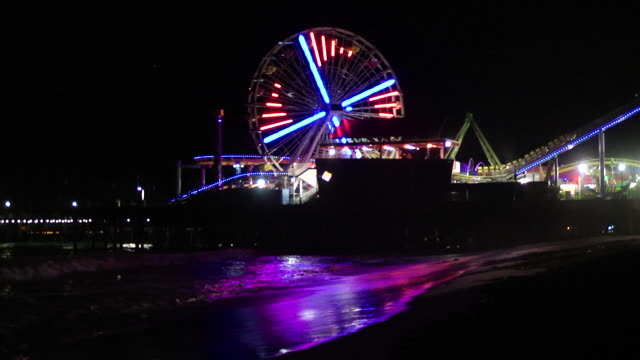 pacific wheel ferris wheel w/ colorful light display turning, partial pirate ship ride & west coaster roller coaster tracks on santa monica pier,... - b roll stock videos & royalty-free footage