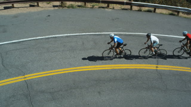 pack of cyclists climbing uphill - spandex stock videos & royalty-free footage