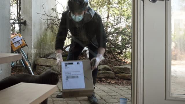 consegna contactless a domicilio del pacco - guanto indumento sportivo protettivo video stock e b–roll